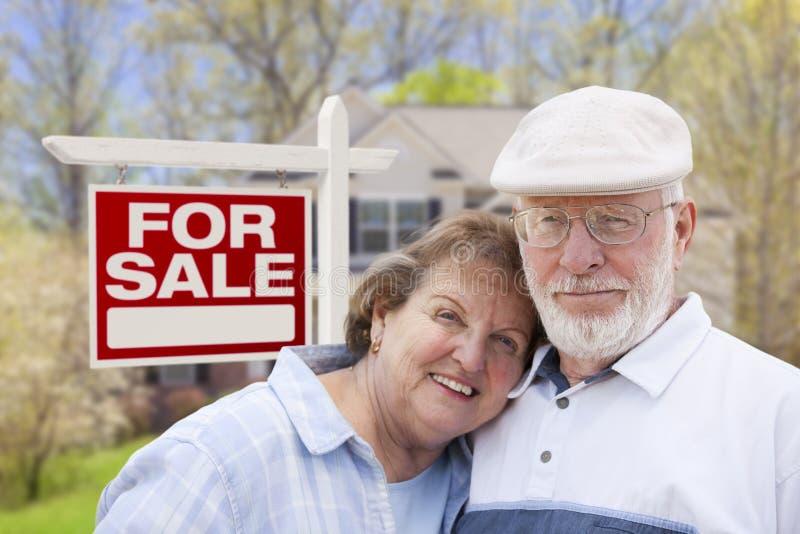 销售标志的和议院愉快的资深夫妇前面  免版税库存图片