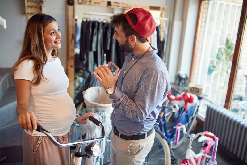 销售自行车-人卖主在自行车商店帮助妇女选择新的自行车 免版税图库摄影