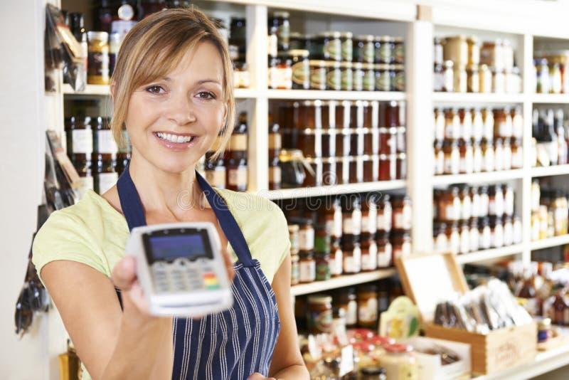 销售辅助在与信用卡机器的食品店 免版税库存照片