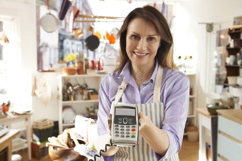 销售辅助在有信用卡机器的Homeware商店 免版税库存图片