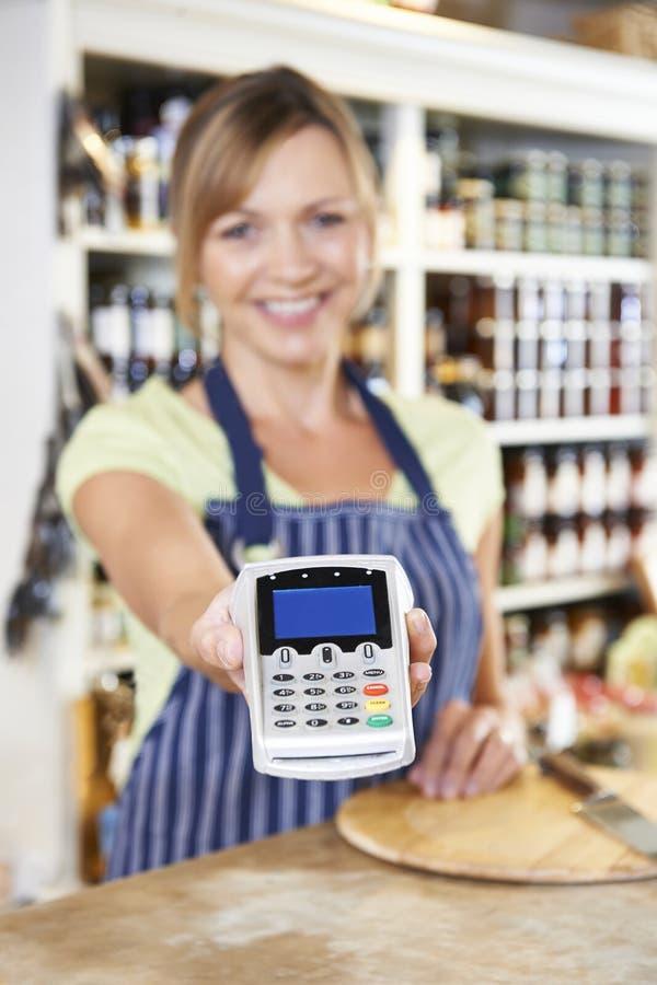 销售辅助在递信用卡机器的食品店对Cus 库存照片