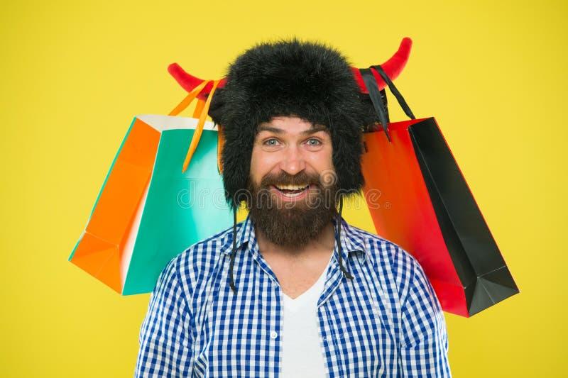 销售,没有等待大的储款 微笑与购买的有胡子的人被买对销售 愉快的行家在公牛角帽子藏品 免版税图库摄影