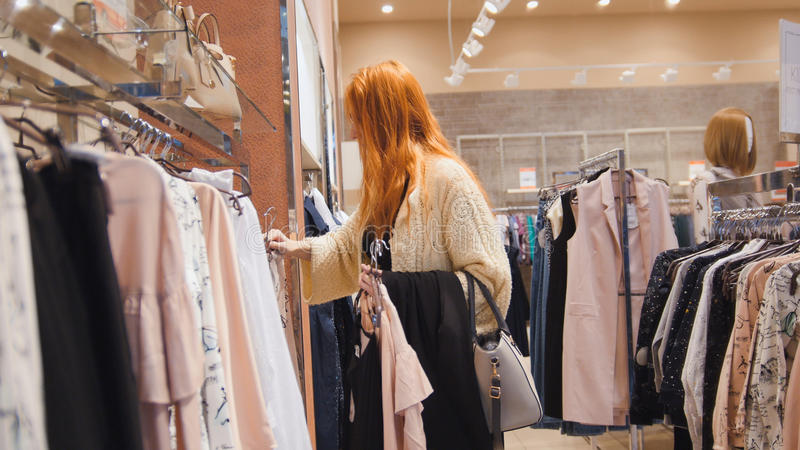 销售-妇女在礼服商店选择衣裳-购物概念 免版税图库摄影