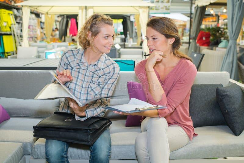 销售respresentative看通过与客户的小册子 库存图片