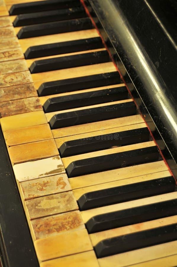 锁上被弄脏的老钢琴 库存图片