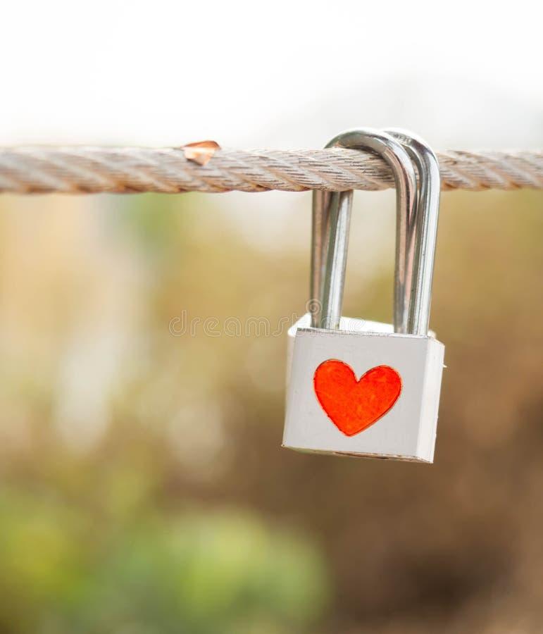 锁与在索桥的心脏标志作为恋人诺言  图库摄影