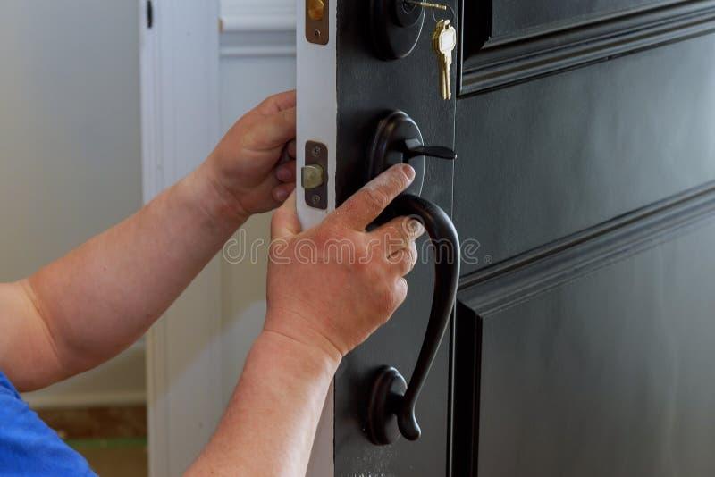 锁设施的木匠有人的hend举行门手把的关闭的 入内部木门 库存图片