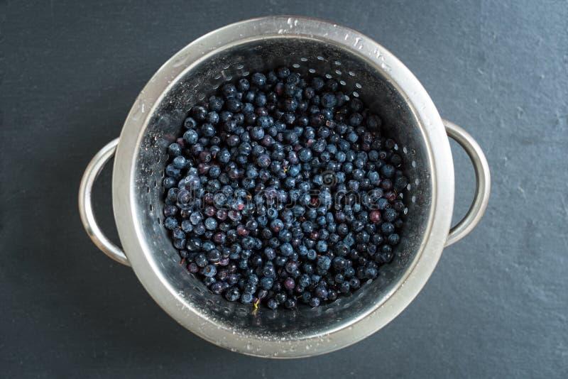 滤锅用在灰色板岩石头板的新近地被洗涤的有机蓝莓 免版税库存照片