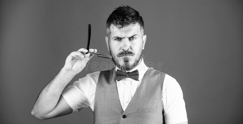 锋利的剃刀 有普通刀片的有胡子的人在理发店 有胡子藏品刮脸剃刀的残酷人 o 免版税库存图片
