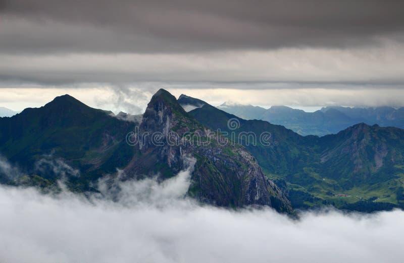锋利的峰顶、绿色山谷在雾和云彩层数Carnic阿尔卑斯 图库摄影