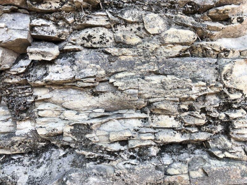 锋利的破裂的老古老石砖凹面概略的自然灰色吹石墙的纹理在岩石的 库存图片