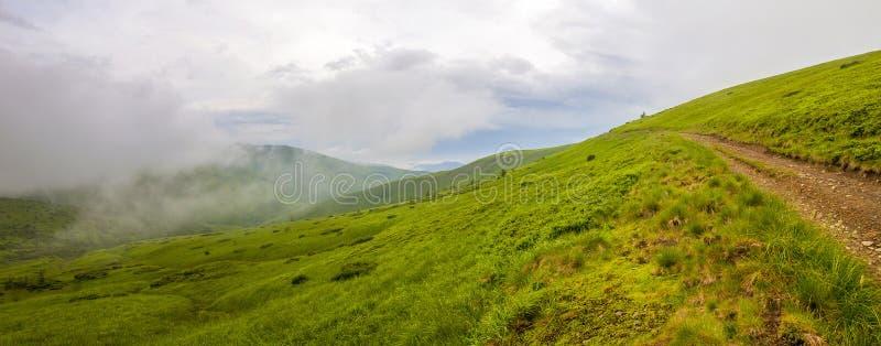 锋利的绿色山峰和天空与剧烈的云彩大局 免版税库存图片