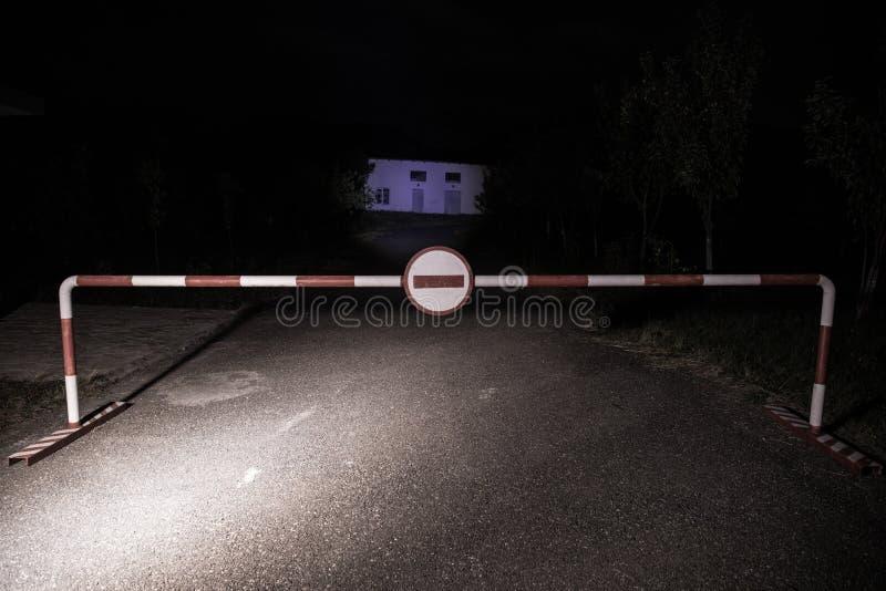 错误方式概念 与标志的障碍没有词条在晚上 站立在路的障碍对与鬼魂或玛尼的可怕被困扰的大厦 免版税图库摄影