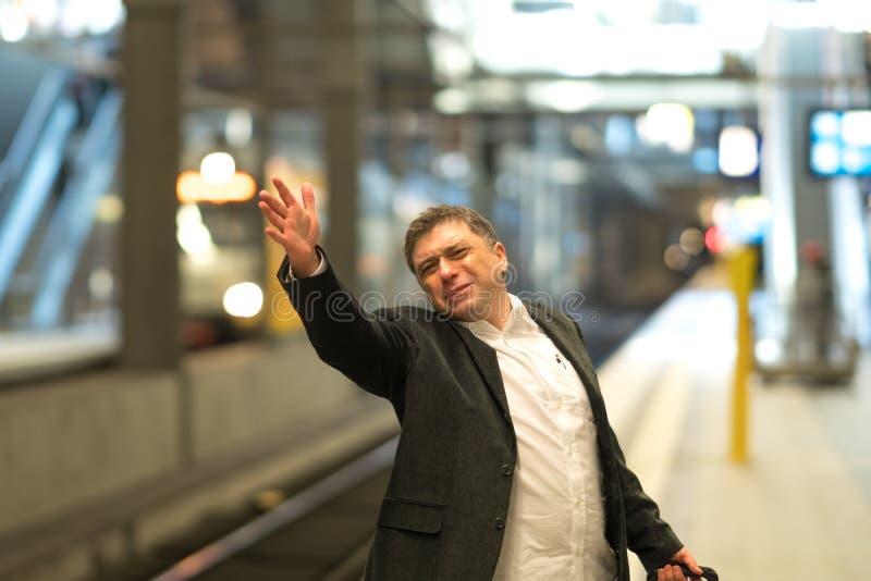 错过他的沮丧的旅行家火车 免版税库存图片