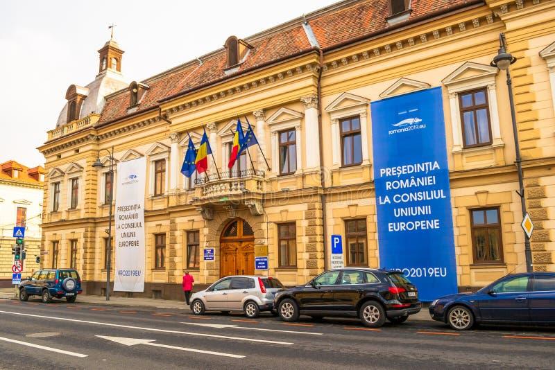 锡比乌县专区Institutia Prefectului Judetului锡比乌外视图,与欧盟委员会横幅的罗马尼亚总统的职务 免版税库存照片