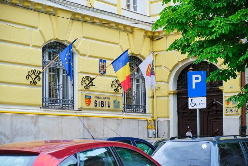锡比乌县委员会Consiliul Judetean锡比乌大厦-外视图在天期间,与罗马尼亚和欧盟旗子  库存照片