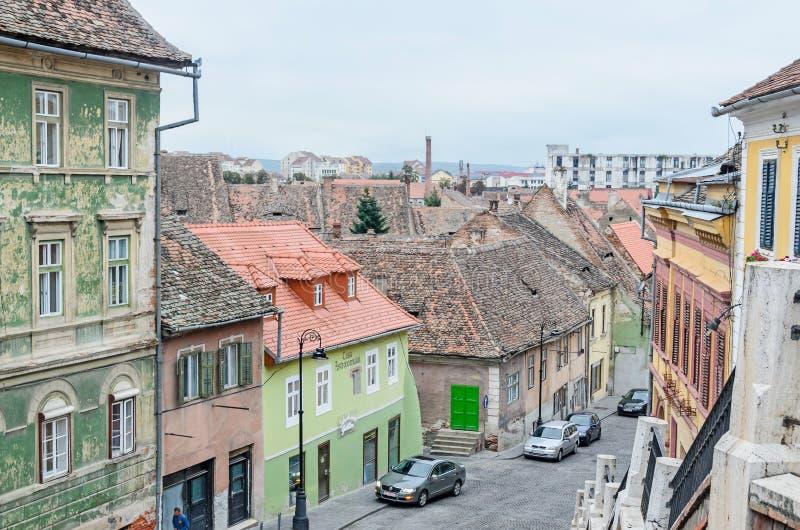 锡比乌,罗马尼亚:街市城市的街道有餐馆和老大厦的,从说谎者桥梁的看法 库存图片