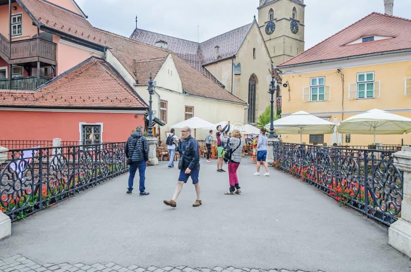 锡比乌,罗马尼亚:说谎者跨接近街市与老色的房子 免版税库存图片