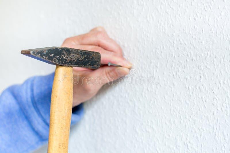 锤击一个钉子入白色墙壁 免版税库存图片