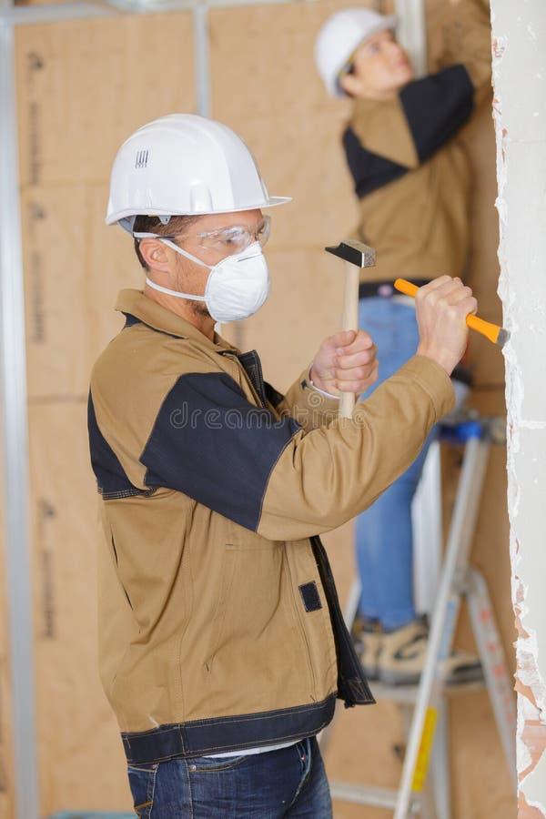 锤击在墙壁上的工作者凿子在建造场所 免版税库存图片