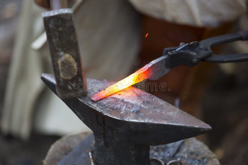 锤击高热金属箭头的铁匠 库存照片