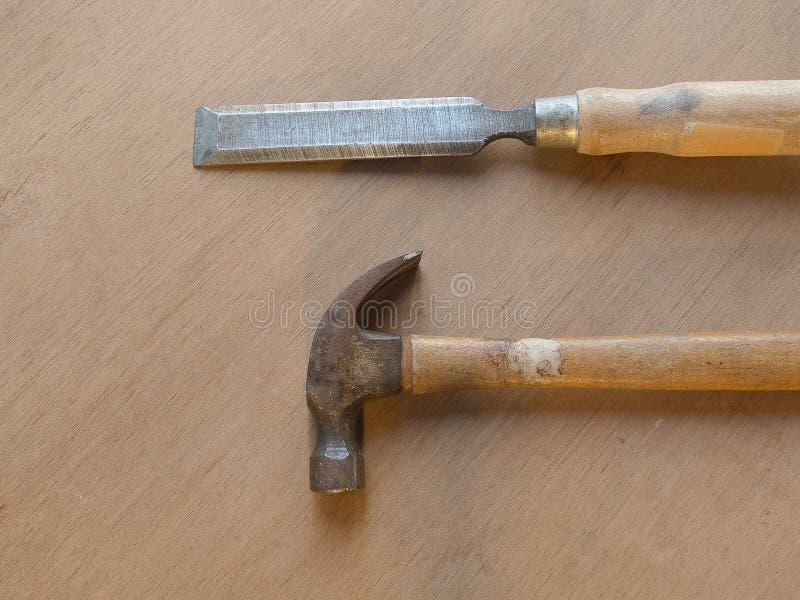锤子和凿子在木桌背景 库存图片
