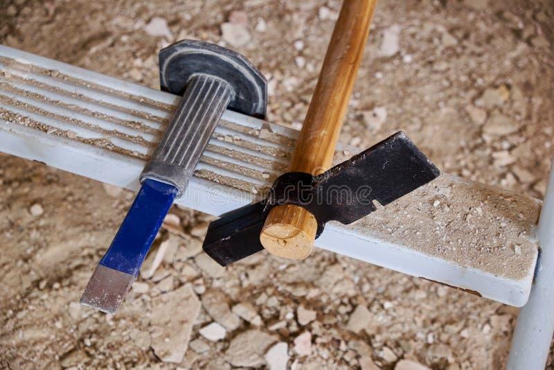 锤子和凿子在梯子和瓦砾 免版税库存图片