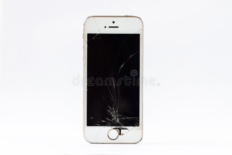 锤击和有一个残破的屏幕的一个智能手机 免版税库存照片