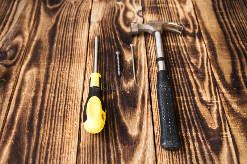 锤击钉子、螺丝和螺丝刀在木背景 库存照片