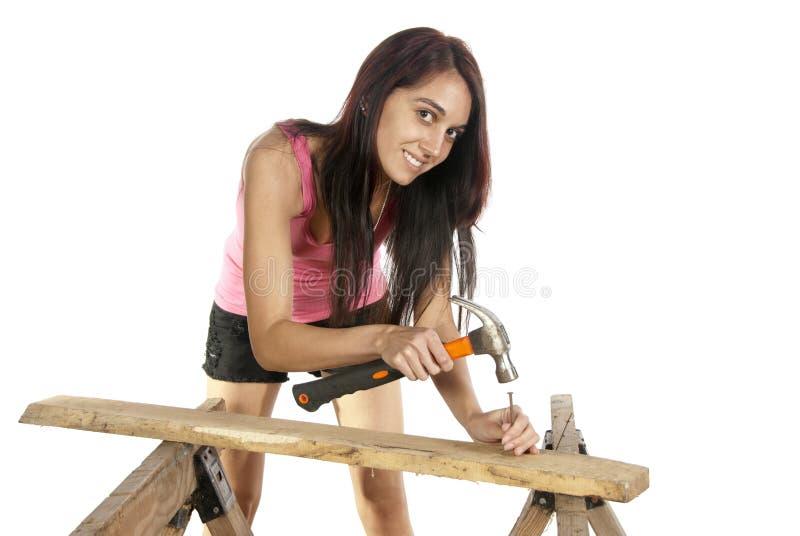 锤击钉子的少妇入木头 库存图片