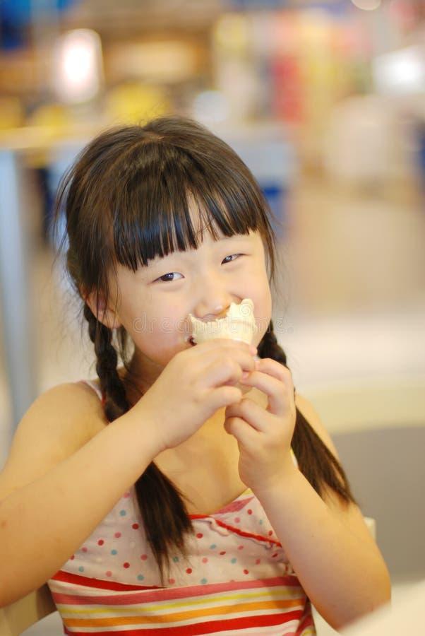 锥体奶油色吃女孩冰 库存照片