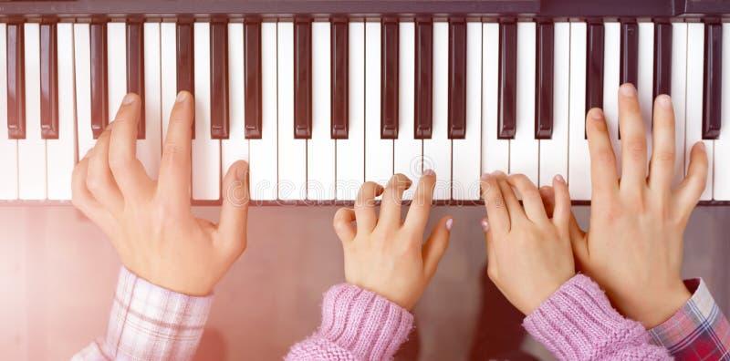 琴键儿童母亲和父亲的顶视图和手 图库摄影