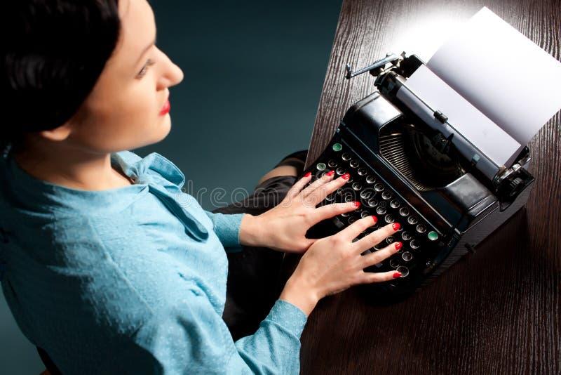 键入与老打字机的少妇 免版税库存图片