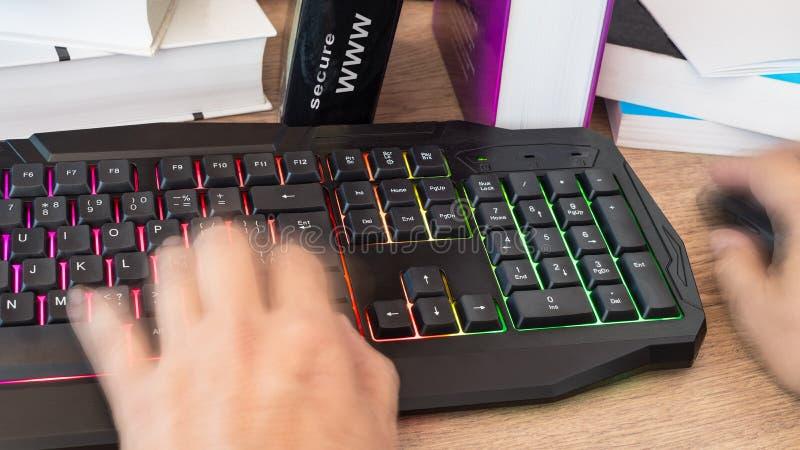 键入在一个色的键盘的手 背景迷离弄脏了抓住飞碟跳的行动 库存照片
