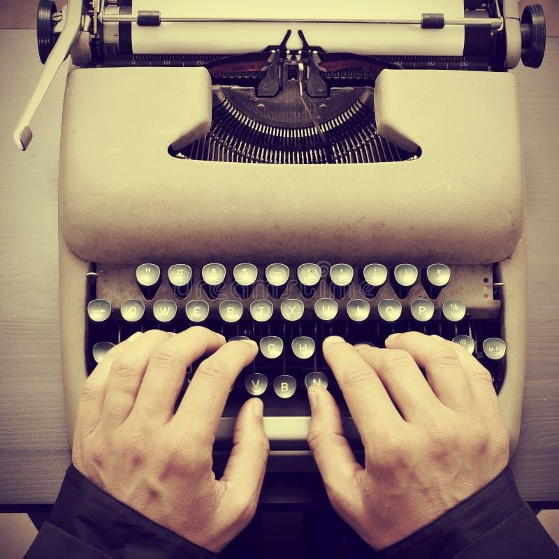 键入在一台老打字机的人 免版税图库摄影