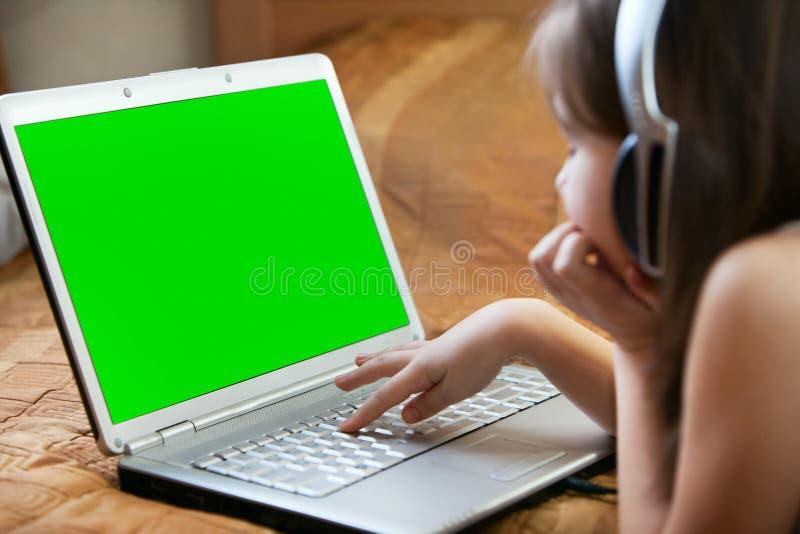 键入在书桌木头的孩子的手键盘 免版税库存图片