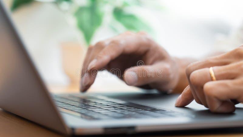 键入在估计坐的表和办公室工具的键盘工作的男性手特写镜头在工作场所,写电子邮件, 免版税库存图片