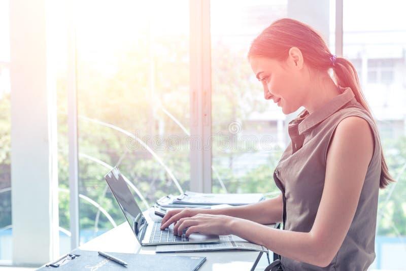 键入在办公室窗口portait侧视图的手提电脑事务的女孩工作 免版税库存图片