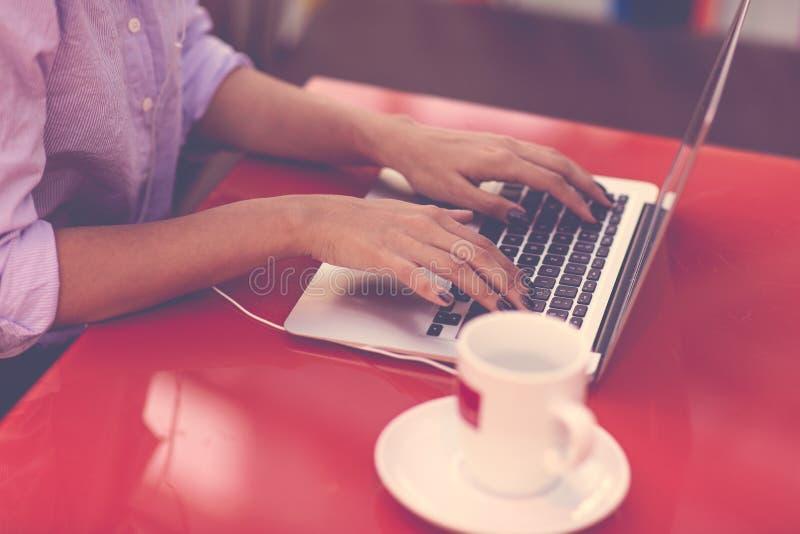 键入在她的手提电脑键盘的妇女的手  女性研究在咖啡馆的膝上型计算机 库存照片