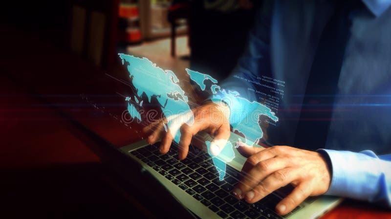 键入在有世界地图全息图的键盘的人 库存图片