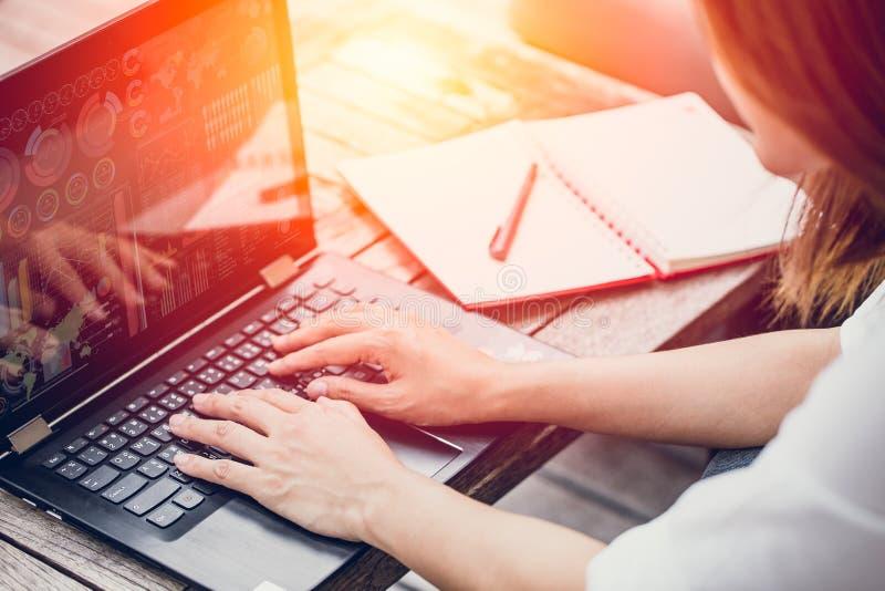 键入在有图表数据的膝上型计算机的亚洲女商人工作在屏幕上 库存图片