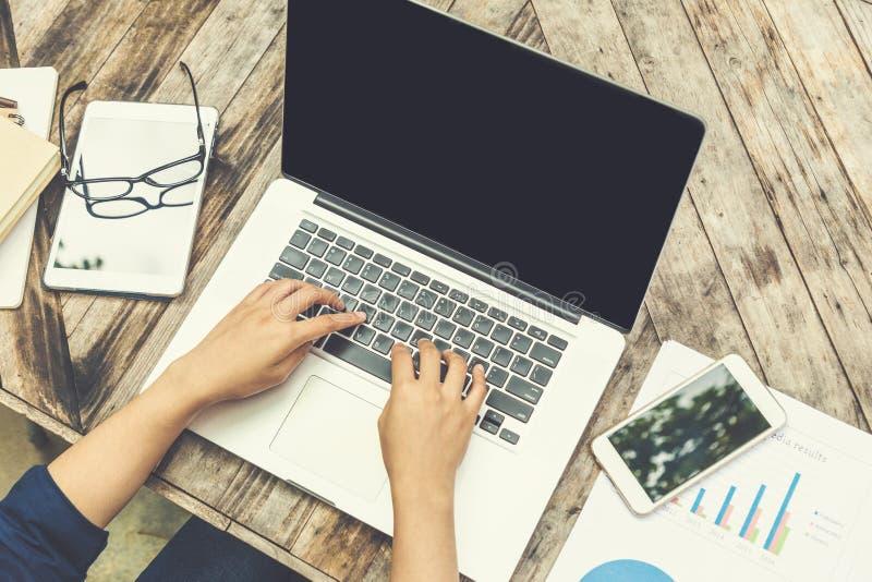 键入在有巧妙的电话的膝上型计算机键盘的女性手在woode 免版税库存照片