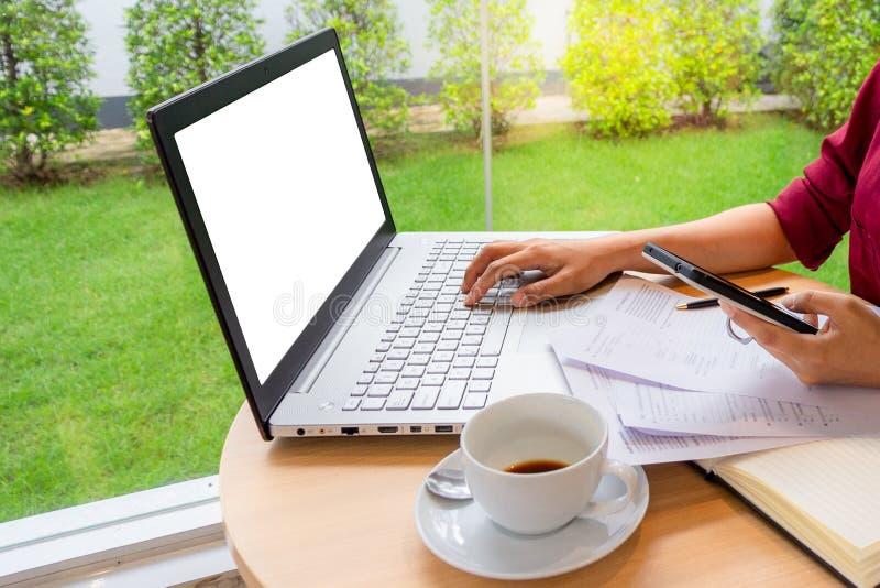 键入在有空白的白色屏幕嘲笑的模板背景和拿着手机与的另一只手的膝上型计算机的女实业家 免版税库存图片