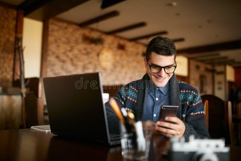 键入在流动现代智能手机的一个年轻人文本 拿着一个现代电话和写电话留言的行家 库存照片