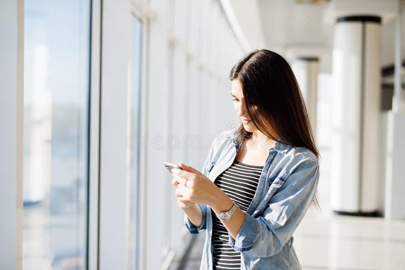 键入在电话和看户外通过窗口的俏丽的女孩 免版税图库摄影