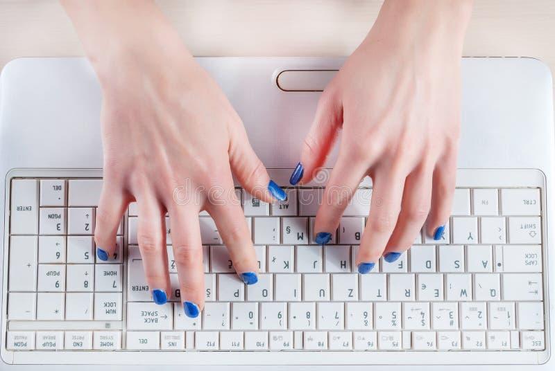 键入在白色膝上型计算机键盘的女性手 图库摄影