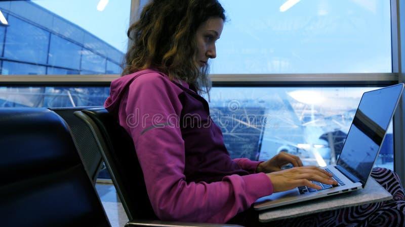 键入在膝上型计算机、等待的飞机和飞行的妇女旅游自由职业者在机场在候诊室 免版税库存照片