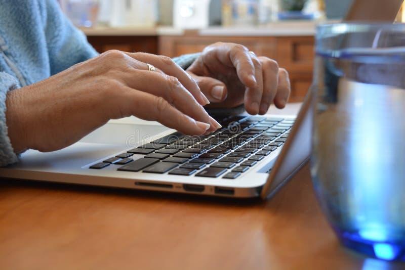 键入在膝上型计算机关键董事会的女商人 库存图片