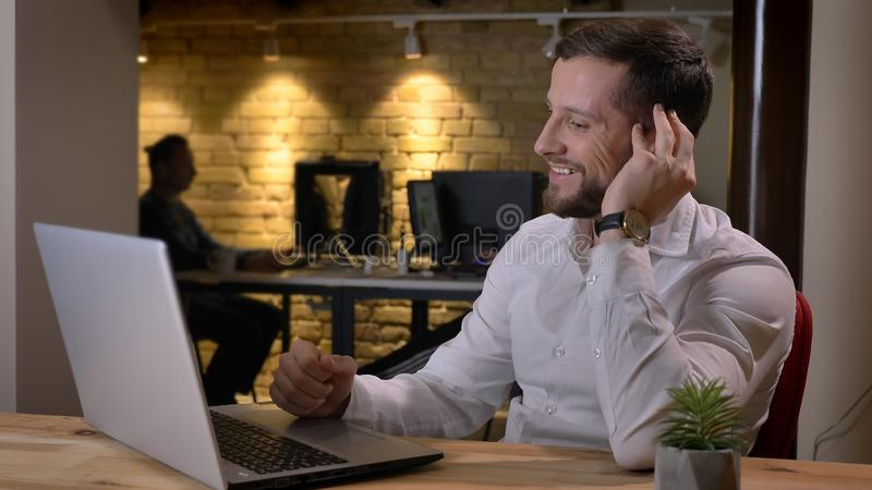 键入在膝上型计算机和微笑满意地的成人白种人成功的商人特写镜头射击户内  免版税库存照片
