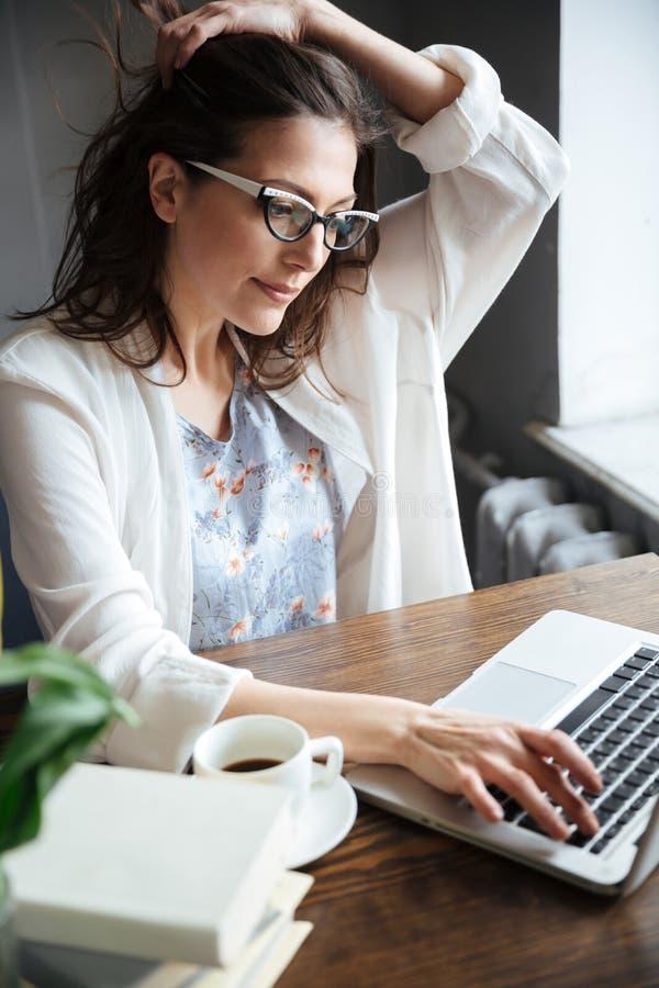 键入在膝上型计算机的一名沉思成熟的商业妇女的画象 库存图片
